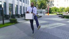 Concept de renvoi de travail, recrutement Un employé marche entre les immeubles de bureaux avec une boîte en carton et banque de vidéos