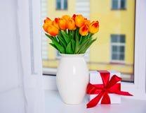 Concept de ressort - beaux tulipes et boîte-cadeau oranges sur un windo Photos stock