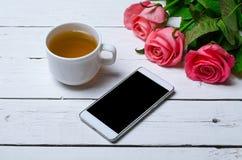 Concept de ressort : une tasse de thé, de fleurs et d'un smartphone sur un vieux Photos stock