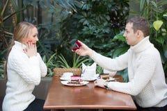 Concept de restaurant, de couples et de vacances - jeune femme enthousiaste regardant l'ami avec la bague de fiançailles Photos stock