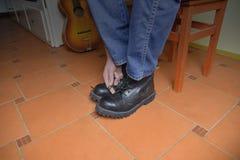 Concept de rock Bottes noires et guitare acoustique Mise sur des bottes de rock photo libre de droits