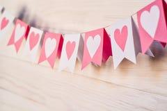 Concept de Saint Valentin hangingon blanc et rose de drapeaux une corde sur le fond rustique blanc Images stock