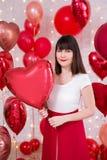 Concept de Saint-Valentin - portrait de jeune belle femme avec les ballons en forme de coeur rouges images stock