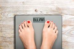Concept de santé et de soin avec le mot de boulimie sur l'échelle de salle de bains tandis qu'une femme pèse photographie stock libre de droits