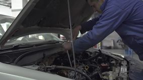 Concept de service, de réparation, d'entretien et de personnes de voiture - homme de mécanicien travaillant à l'atelier Mouvement banque de vidéos