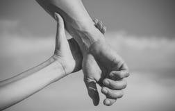 Concept de soin et d'amour Deux mains sur le ciel bleu Photos stock