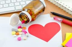 Concept de soins de santé - papier de note rouge de coeur avec le supplément Photo stock