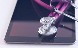 Concept de soins de santé et de technologie - marquez sur tablette le PC, le stéthoscope et le comprimé sur la table Photographie stock