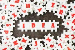 Concept de solution d'idée, de créativité ou d'affaires, puzzle blanc de puzzle avec l'alphabet établissant l'idée de mot au cent image libre de droits
