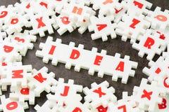 Concept de solution d'idée, de créativité ou d'affaires, puzzle blanc de puzzle avec l'alphabet établissant l'idée de mot au cent photographie stock libre de droits