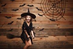 Concept de sorcière de Halloween - petit vol caucasien d'enfant de sorcière sur le manche à balai magique au-dessus du fond de to photo stock