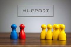 Concept de soutien avec des figurines de gage sur la table Photos libres de droits