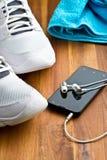 Concept de sport écouteurs, chaussures et serviette Photo stock
