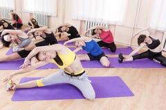 Concept de sport et de forme physique Groupe de sept athlètes féminins exécutant étirant l'exercice Photos stock