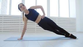 Concept de sport et de forme physique à la maison Jeune femme faisant des exercices de forme physique dans un intérieur blanc banque de vidéos