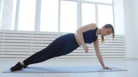 Concept de sport et de forme physique à la maison Jeune femme faisant des exercices de forme physique dans un intérieur blanc clips vidéos