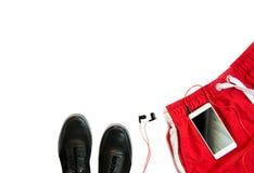Concept de sport Objets courants Shorts rouges, espadrilles, chapeau et téléphone avec des écouteurs Vue supérieure images stock