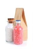 Concept de station thermale avec des bouteilles de sel de bain coloré une serviette bleue et un sac de papier Photographie stock libre de droits
