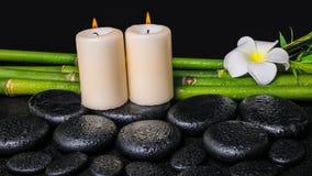 Concept de station thermale des pierres de basalte de zen, plumeria de fleur blanche, bougies Photos stock