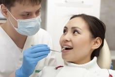 Concept de stomatologie - dentiste masculin avec le miroir vérifiant le patient image libre de droits