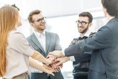 Concept de succès dans les affaires : équipe amicale d'affaires se tenant en cercle et joignant ses mains ensemble Photographie stock libre de droits