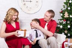 Concept de surprise - parents donnant des présents à leur fils dans l'avant Photo libre de droits