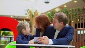 Concept de technologie et de personnes Le père avec la vidéo de montre de fils au téléphone La mère approche la famille d'un dos banque de vidéos