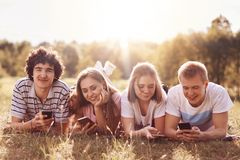 Concept de technologie, de jeunesse et de temps libre Les quatre amis heureux utilisent les téléphones portables, mensonge sur l' Photographie stock