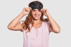 Concept de temps de lit La jeune femelle européenne heureuse avec plaisir avec le sourire toothy, masque de sommeil de contacts,  images stock