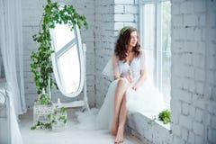 Concept de tendresse et de sensualité Pose modèle de belle brune sur le lit dans la lingerie blanche Portrait sensuel des jeunes Image stock