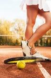 Concept de tennis avec la boule, la fabrication, la raquette et les jambes sexy de femme Image libre de droits