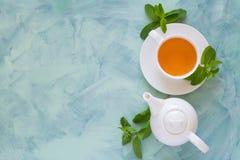Concept de thé La théière et la tasse avec la tisane verte ont décoré les feuilles en bon état Image libre de droits