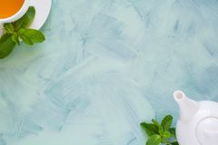 Concept de thé La théière et la tasse avec la tisane verte ont décoré les feuilles en bon état Photographie stock