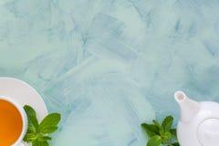 Concept de thé La théière et la tasse avec la tisane verte ont décoré les feuilles en bon état Image stock