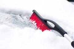 Concept de transport, d'hiver, de temps, de personnes et de véhicule - équipez la neige de nettoyage de la voiture avec la brosse Photo stock