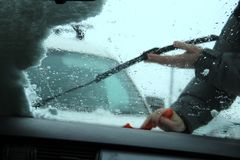 Concept de transport, d'hiver, de temps, de personnes et de véhicule - équipez la neige de nettoyage de la voiture avec le gratto Image libre de droits