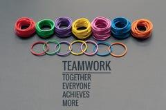 Concept de travail d'équipe le groupe d'une bande élastique colorée sur le fond noir avec le travail d'équipe de mot, ensemble, c Image libre de droits