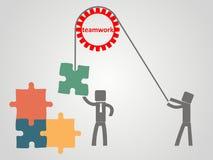 Concept de travail d'équipe - un employé soulève des puzzles sur une corde Photos stock