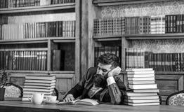 Concept de travail intellectuel L'homme barbu dans la bibliothèque a le travail intellectuel images libres de droits