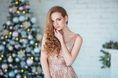 Concept de vacances, de célébration et de personnes - jeune femme dans la robe élégante au-dessus du fond d'intérieur de Noël Photo stock