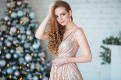 Concept de vacances, de célébration et de personnes - jeune femme dans la robe élégante au-dessus du fond d'intérieur de Noël Photographie stock libre de droits