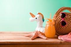 Concept de vacances d'été avec le jus d'ananas, les accessoires de plage et le flotteur de piscine de licorne sur le fond en bois images stock