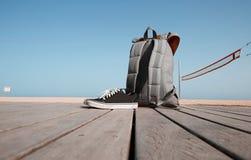 Concept de vacances d'été Le sac à dos et les espadrilles sont sur le bureau en bois près de la plage et de la mer Ciel et soleil Images libres de droits