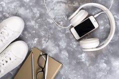 Concept de vacances d'été : smartphone, espadrilles blanches, bloc-notes, écouteurs, stylo Image libre de droits