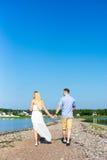 Concept de vacances d'été - vue arrière des couples marchant sur le bea Images stock