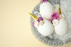 Concept de vacances de Pâques avec la décoration faite main mignonne d'oeufs, de licorne et de fleur dans le nid d'oiseau image stock