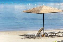 Concept de vacances - parapluies et lits pliants de plage sur une plage sablonneuse Photographie stock