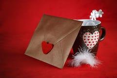 Concept de Valentine, lettre d'amour, et une tasse de coeur sur un fond rouge Image stock