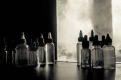 Concept de Vape Nuages de fumée et bouteilles liquides de vape sur la fenêtre avec la lumière du soleil sur le fond Effets de la  Photographie stock
