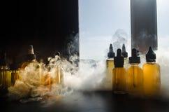 Concept de Vape Nuages de fumée et bouteilles liquides de vape sur la fenêtre avec la lumière du soleil sur le fond Effets de la  Photographie stock libre de droits